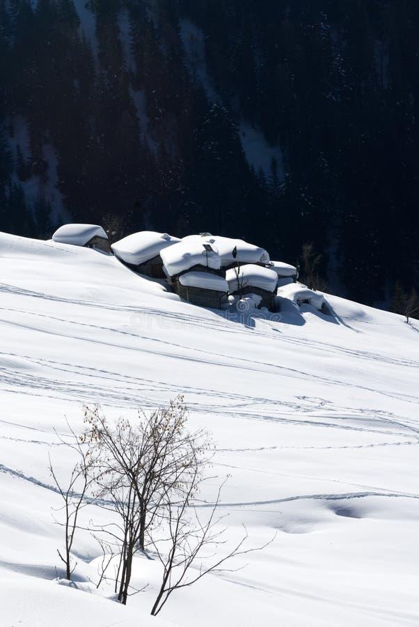 Aldea alpestre bajo nieve fotos de archivo