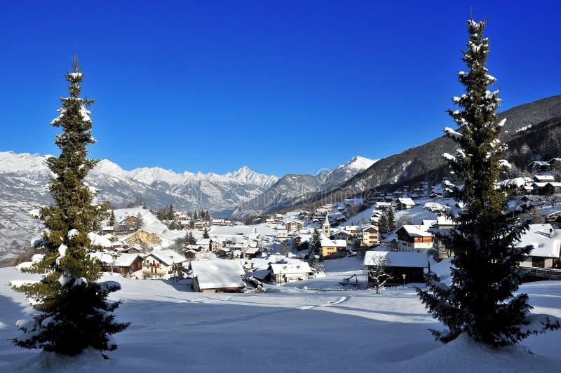 Aldea en las montan@as suizas enmarcadas por los árboles de pino fotografía de archivo