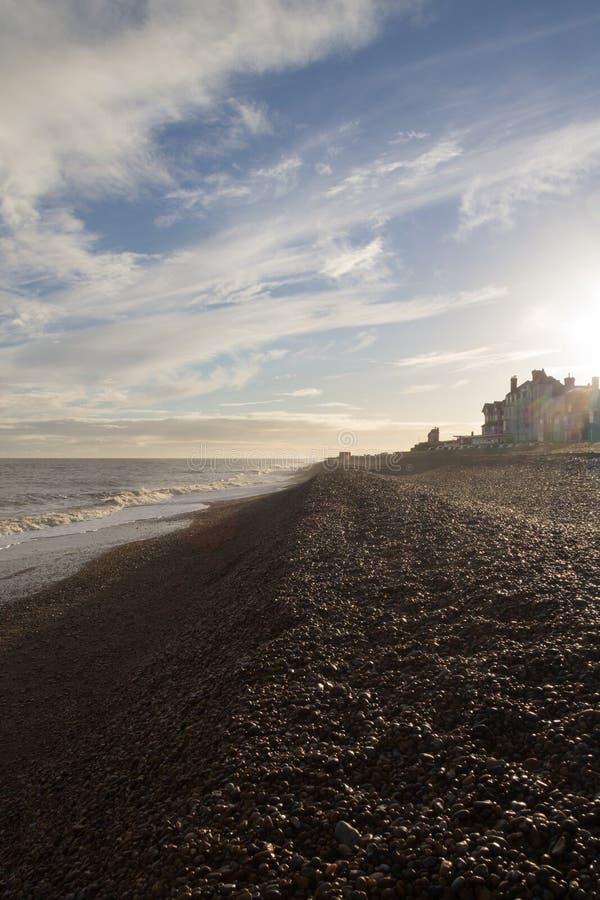 Aldeburgh shingle beach bright sun in winter with lens flare. In Suffolk stock photos