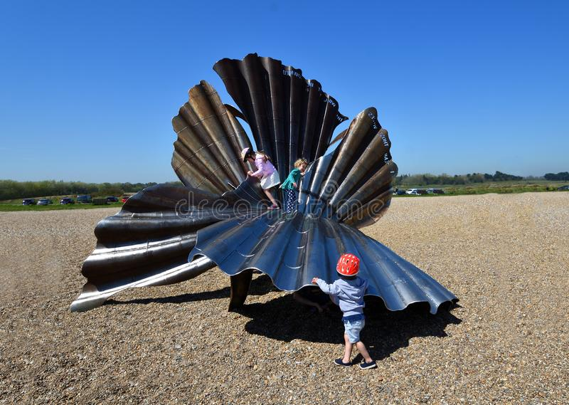 Scallop Shell Sculpture on Aldeburgh Beach with Children climbing on it. ALDEBURGH, SUFFOLK, ENGLAND - MAY 05, 2018: Scallop Shell Sculpture on Aldeburgh Beach stock photos