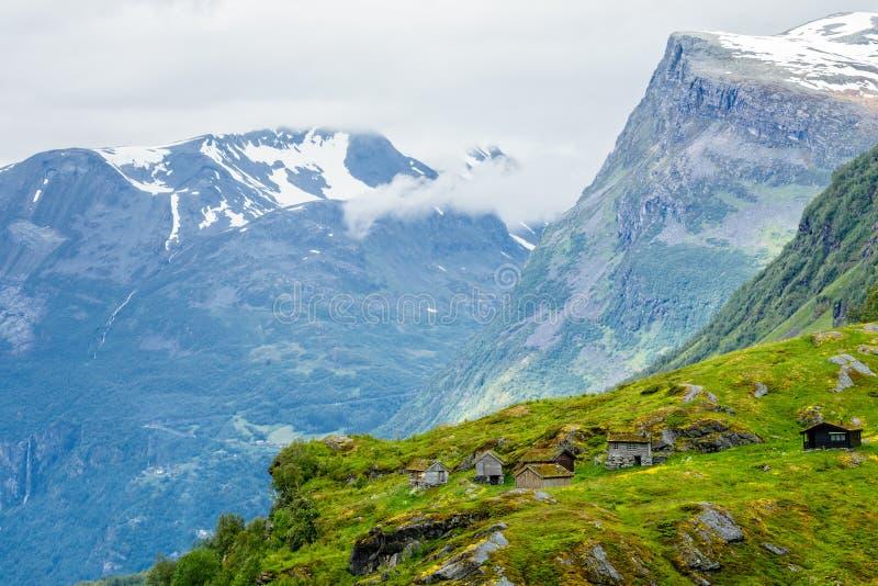 Aldeia da montanha norueguesa com as casas tradicionais do telhado do relvado, Geiranger, região de Sunnmore, mais condado de Rom foto de stock