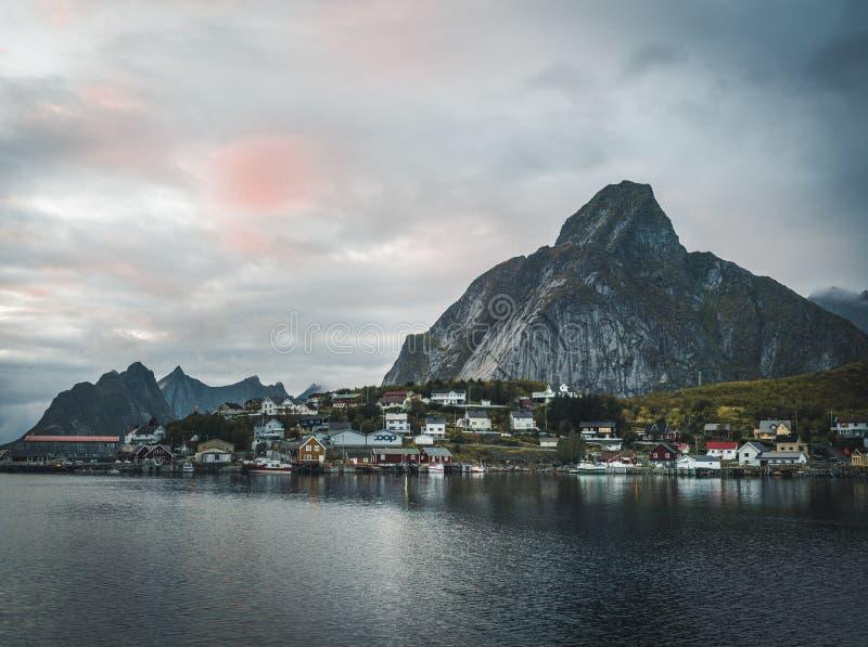 Aldeia piscatória norueguesa Reine nas ilhas de Lofoten em Noruega Nuvens dramáticas do por do sol que movem-se sobre a montanha  imagem de stock