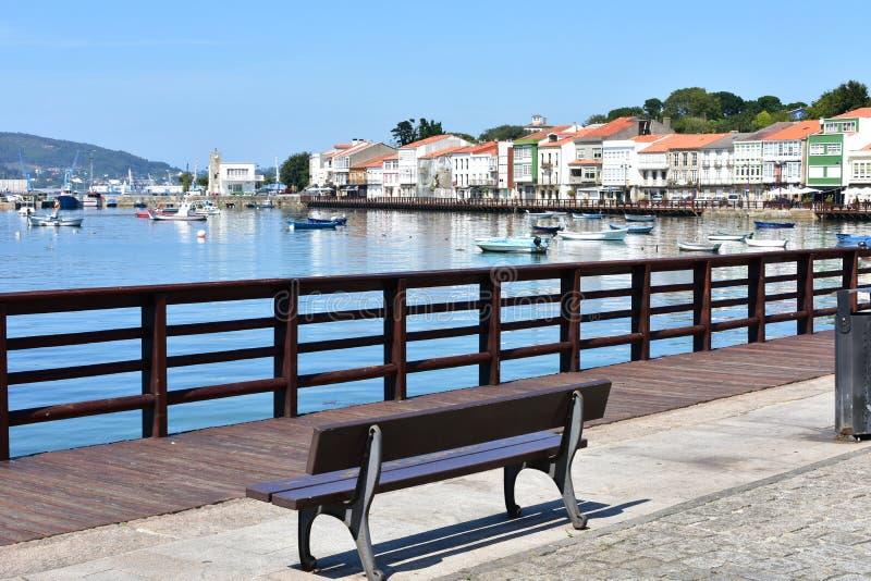Aldeia piscatória pequena com passeio à beira mar e o banco de madeira Céu azul, dia ensolarado, Mugardos, Espanha imagem de stock