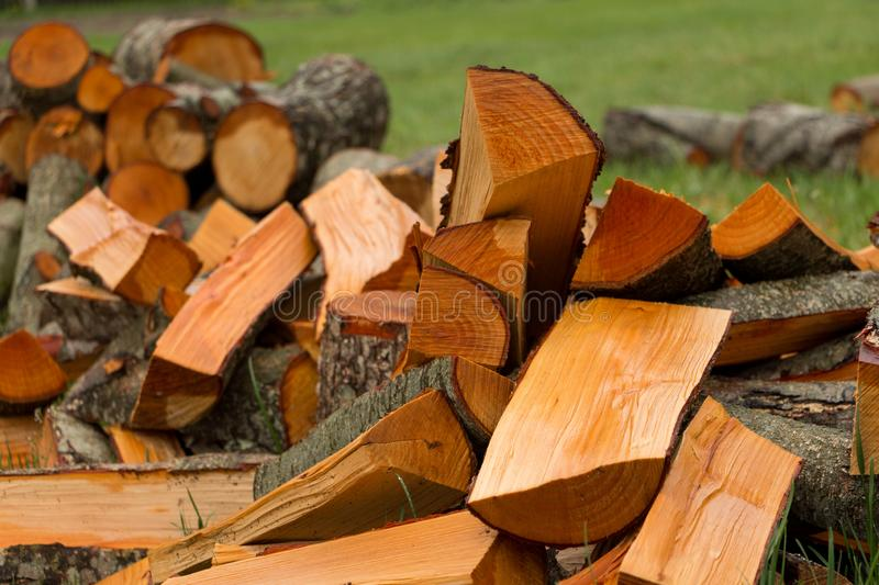 Alder firewood on the grass. Cutting wood in the countryside natural log stack fuel pile chopping block timber wooden axe woodfuel tree lay woodpile forest royalty free stock photo