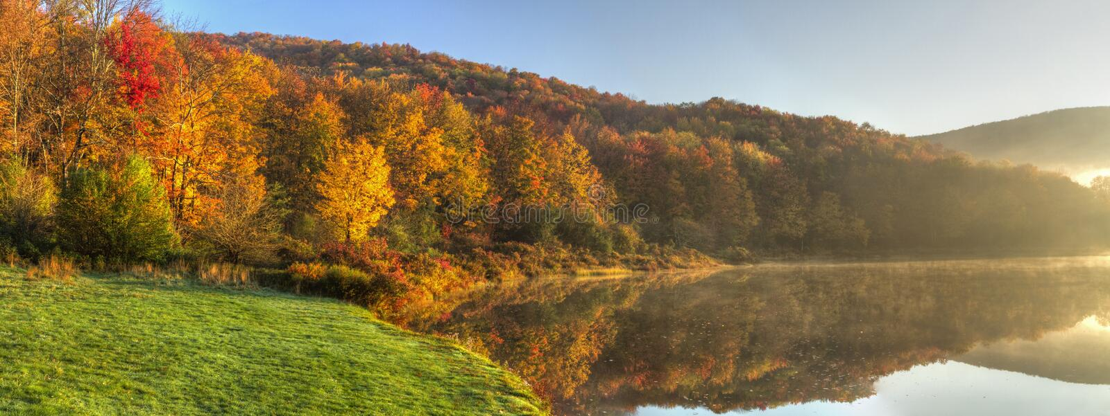 Alder Lake Morning Fog Panorama. Sunlight burning off the morning fog on Alder Lake on a colorful Autumn day in the Catskills Mountains of New York royalty free stock photos