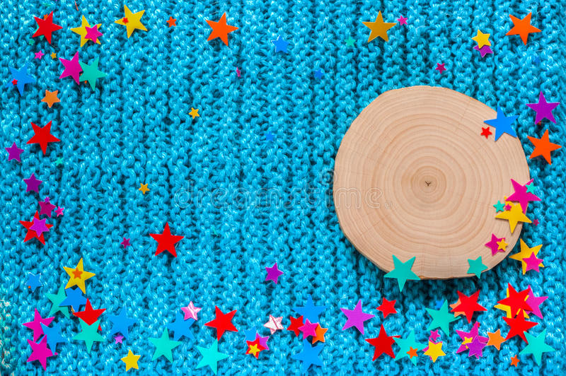 Alder saw cut and the colored stars on a blue knit background. New year and Christmas background royalty free stock images