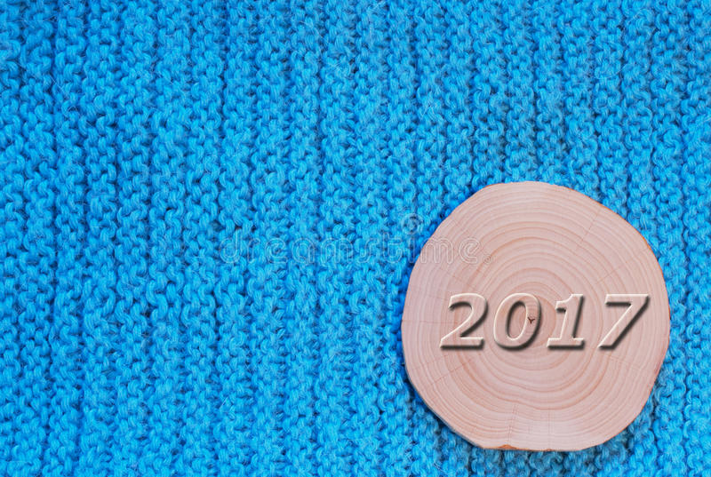 Alder saw cut and convex date in 2017 against the backdrop of th. E blue knitted fabric. New Year`s and Christmas background royalty free stock images