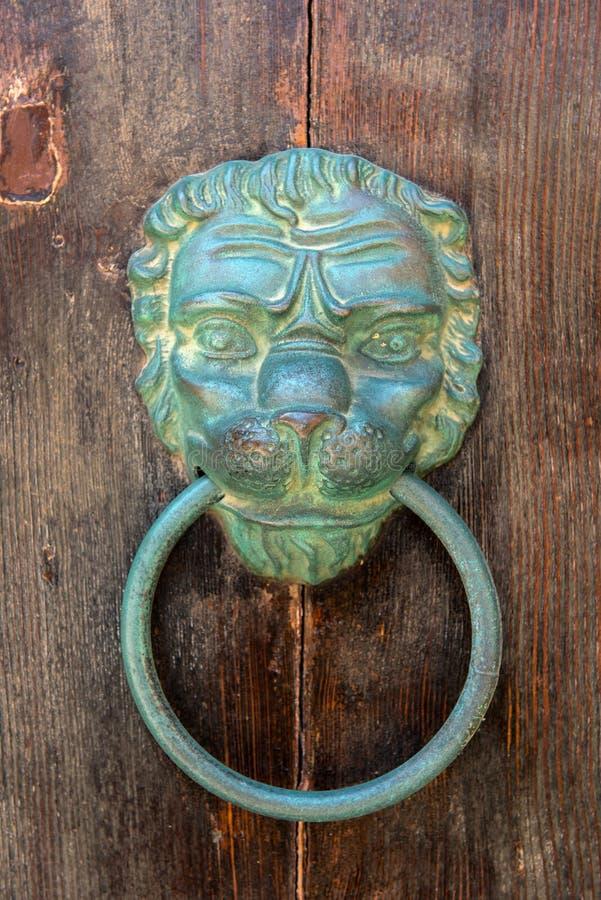 Aldrava de porta de bronze velha da cabeça do leão em uma porta de madeira foto de stock