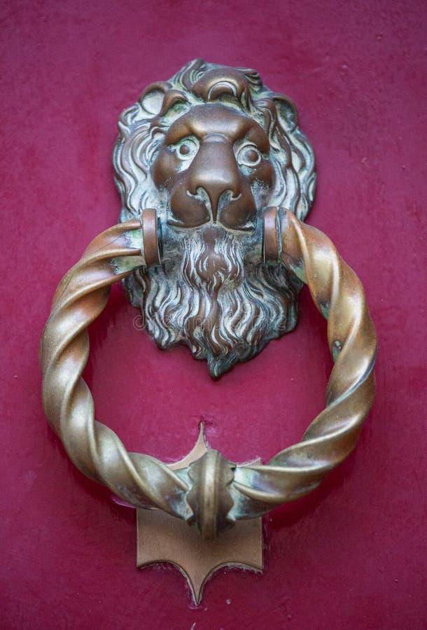Aldrava de porta principal do leão dourado velho do ferro em uma porta cor-de-rosa de madeira Mdina, Malta imagem de stock