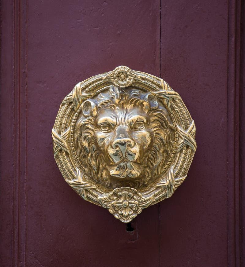 Aldrava de porta principal do leão dourado velho do ferro em uma porta de madeira Mdina, Malta imagem de stock
