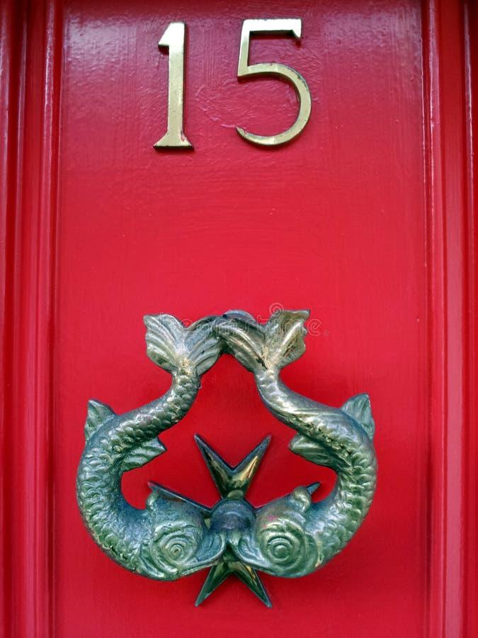 A aldrava na porta vermelha número 15 com Peixes pesca imagens de stock royalty free