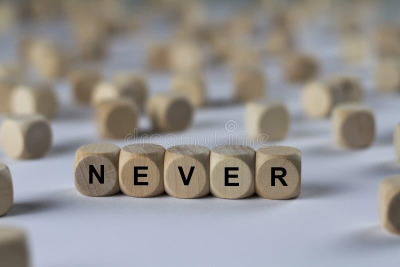 Aldrig - kub med bokstäver, tecken med träkuber fotografering för bildbyråer