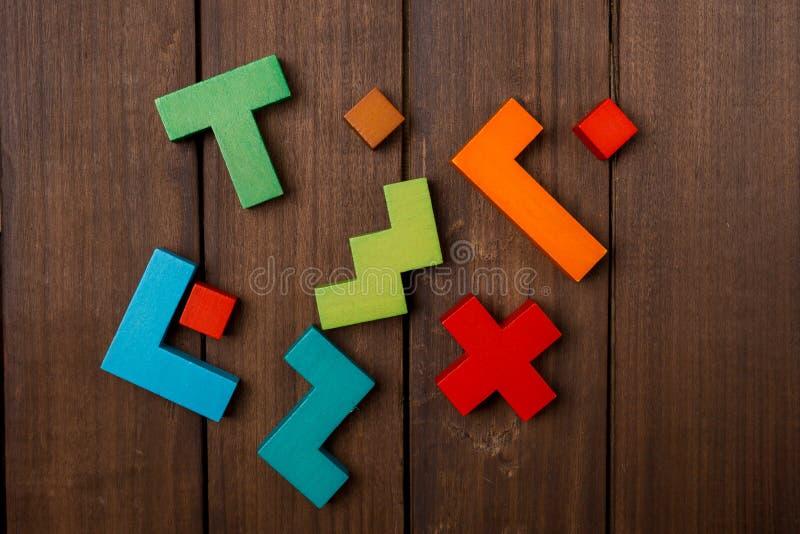 Aleatoriamente partes do jogo lógico de madeira na tabela marrom de madeira Copie o espaço foto de stock