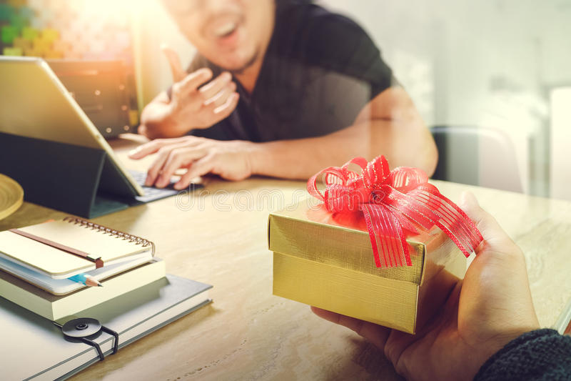Alegría del donante de la Navidad mano creativa del diseñador del negocio que da a su colega foto de archivo