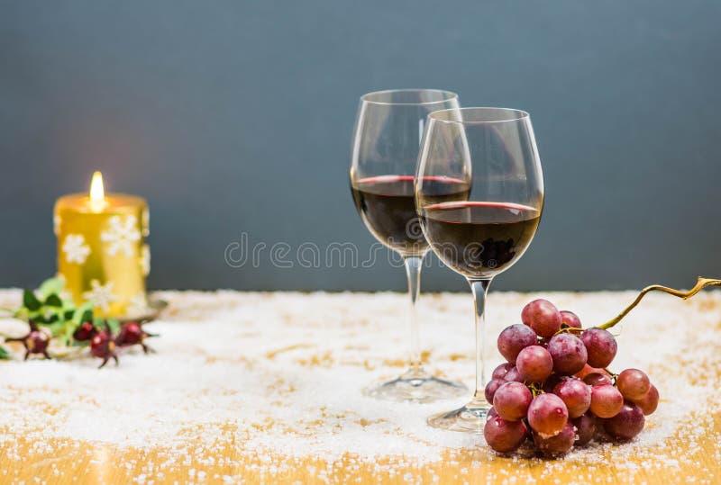 Alegrías de la Noche Vieja con dos vidrios de vino rojo y de uvas imágenes de archivo libres de regalías