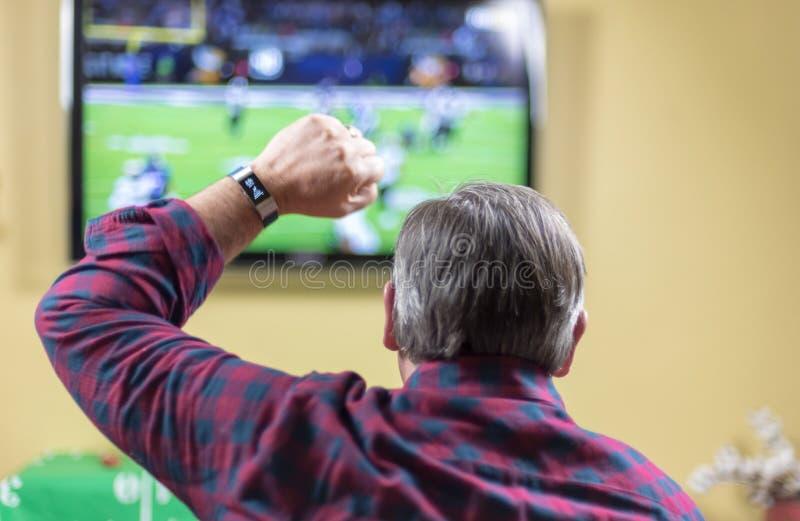 Alegrías del hombre para el equipo mientras que mira el partido de fútbol en la TV imagen de archivo