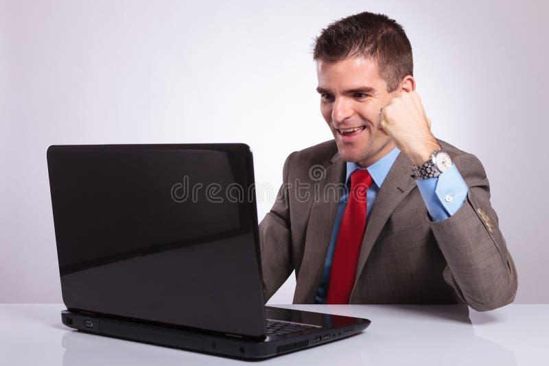 Alegrías jovenes del hombre de negocios mientras que lee en el ordenador portátil imagen de archivo libre de regalías