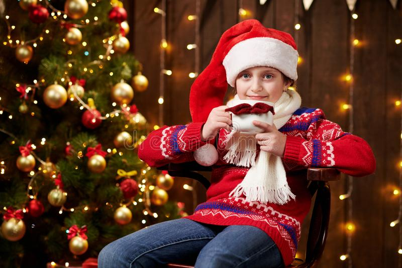Alegre ayudante de santa con una taza de té sentada en el interior cerca de un árbol de Navidad decorado con luces, vestido con  foto de archivo