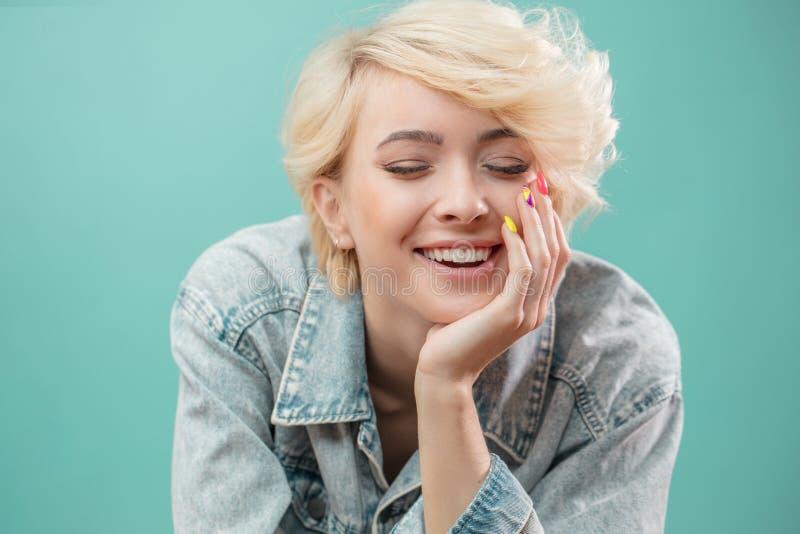 alegre el blonde feliz se está inclinando en su mano imagen de archivo