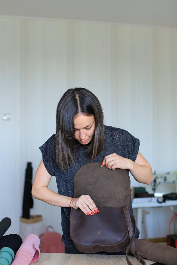 Alegre a la mujer que hace el bolso hecho a mano de cuero marrón en el taller imagen de archivo libre de regalías