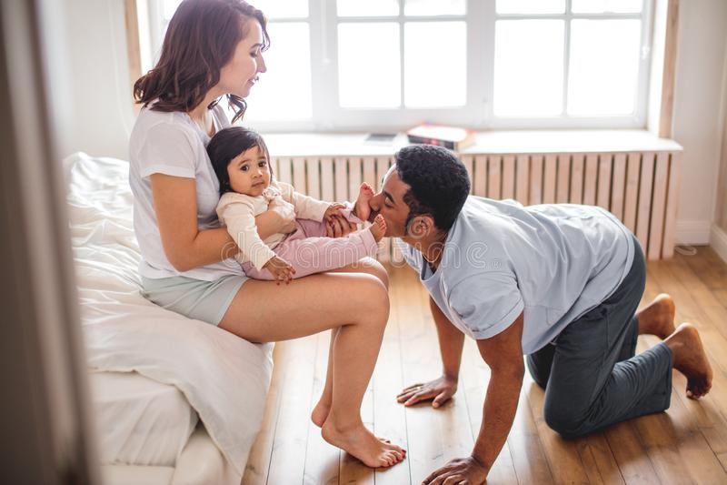 Alegre una madre que abraza su hijo y padre que se besan los dedos del pie fotografía de archivo