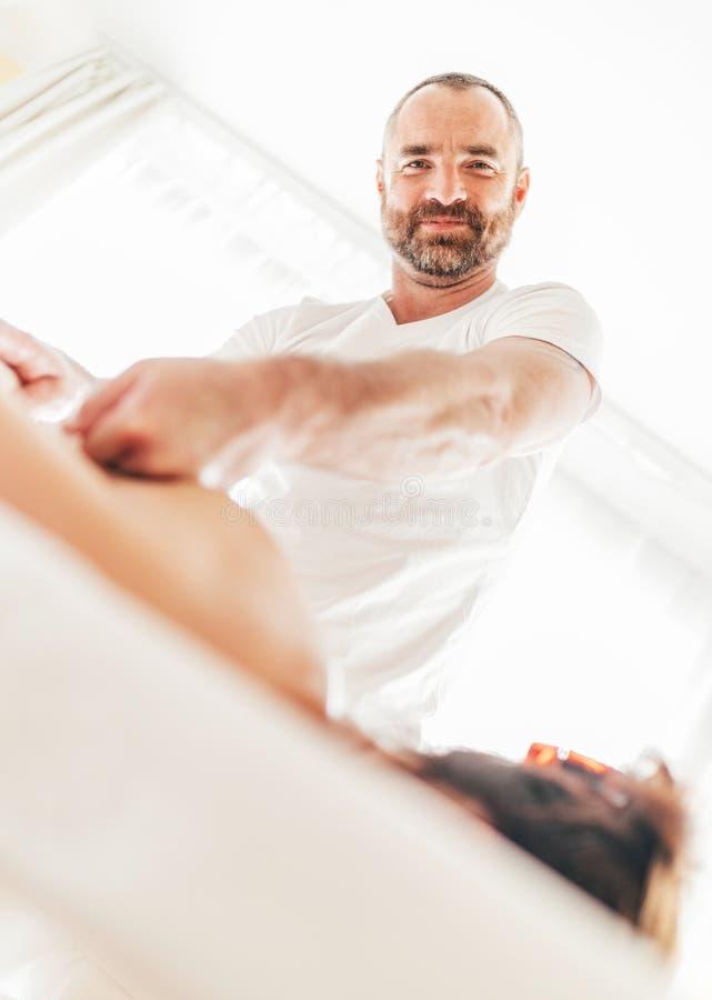 Alegremente sorrindo no homem farpado do massagista da câmera que faz manipulações da massagem na zona da área da omoplata durant imagens de stock royalty free