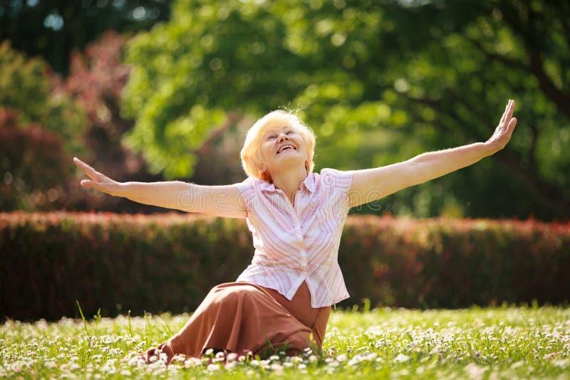 Alegria. Meditação. Mulher satisfeito madura que relaxa com braços extendidos fotos de stock
