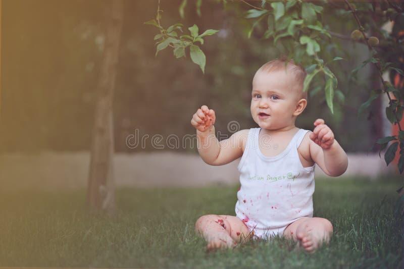 Alegria pura - bebê feliz bonito com morango imagens de stock