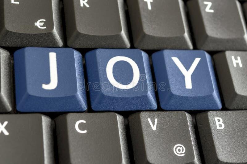 Alegria soletrada no teclado de computador foto de stock