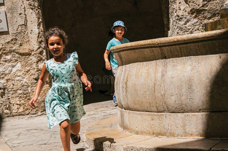Aleia com arcos, as crianças e a fonte de pedra no Saint-Paul-de-Vence imagens de stock royalty free