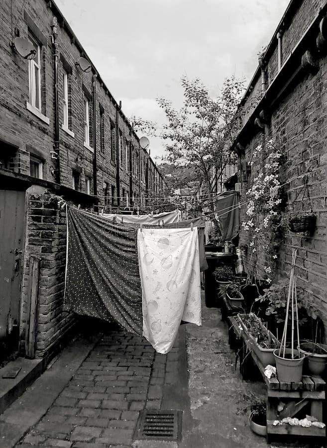 A aleia traseira de casas terraced britânicas tradicionais com lavagem em linhas e as plantas em uns potenciômetros recolhidos he foto de stock