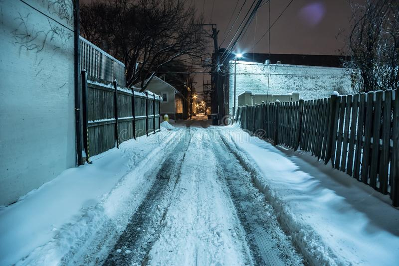 Aleia urbana escura coberto de neve da cidade no inverno na noite imagem de stock