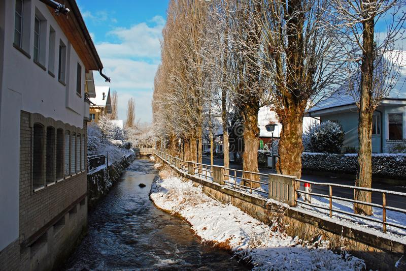 Aleja z śniegiem obok Lyssbach strumyka w mieście Lyss, mały Szwajcarski miasto fotografia stock