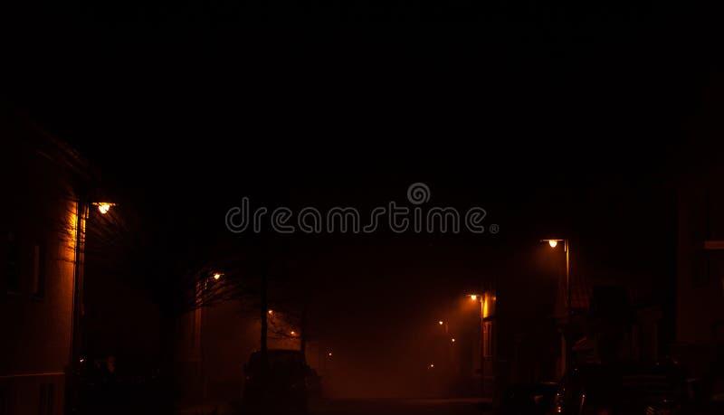 Alemanha na noite - uma rua nevoenta, escura em uma cidade pequena iluminada por uma luz alaranjada fraca de lâmpadas da noite fotografia de stock