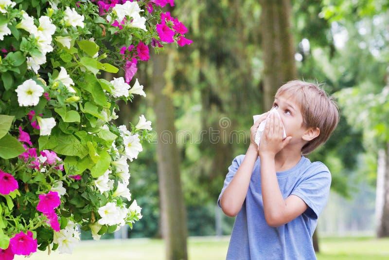 alergia Chłopiec dmucha jego nos blisko drzewa w kwiacie obraz stock