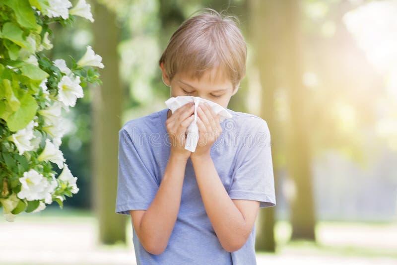 alergia Chłopiec dmucha jego nos blisko drzewa w kwiacie obraz royalty free