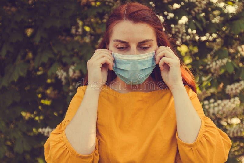 Alergia a los ?rboles de florecimiento Mujer con el pelo rojo y una máscara para la protección contra infecciones y virus en la c imágenes de archivo libres de regalías