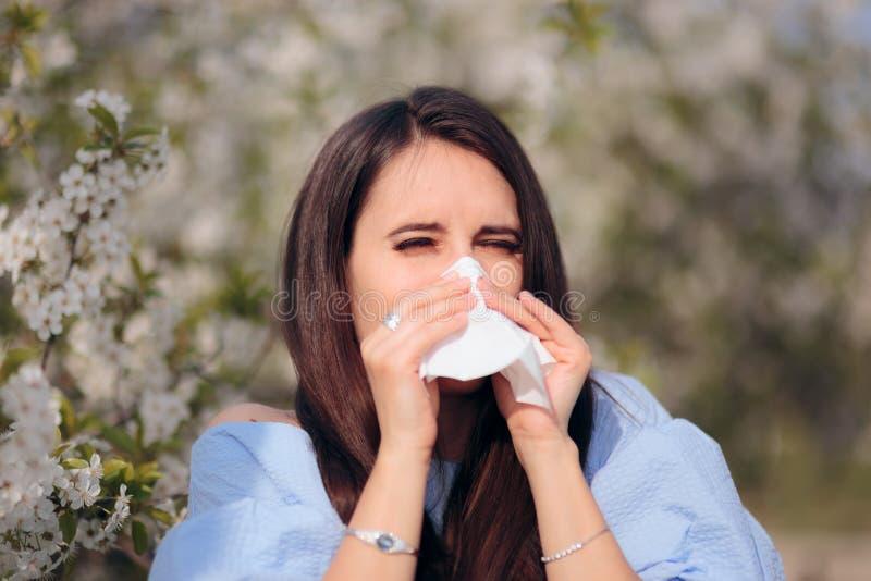 Alergiczna kobieta Dmucha Jej nos Obok Kwitnącego drzewa zdjęcie royalty free