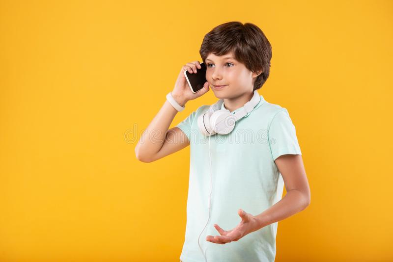 Alert child talking on the phone. Communicating. Cheerful dark-haired boy smiling while talking on the phone stock photos