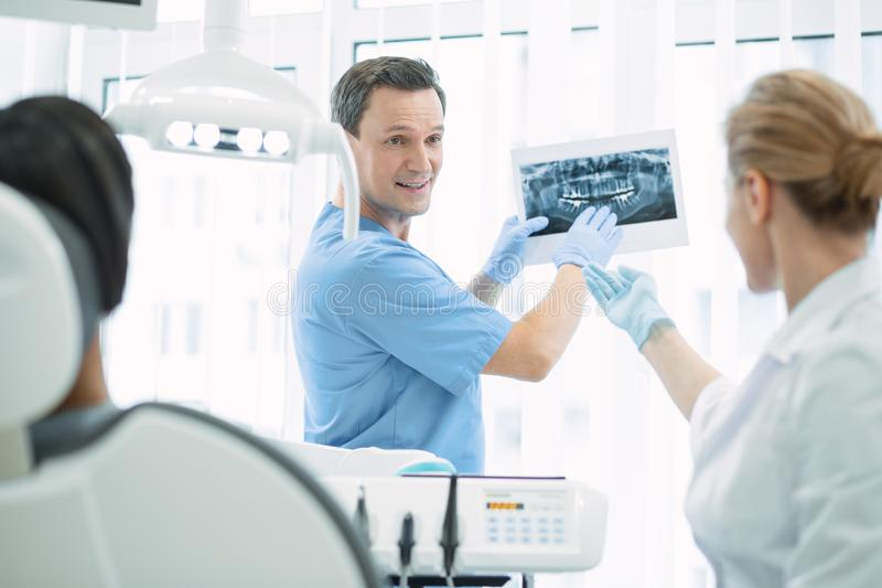 Alert dentist showing teeth on the screen stock image