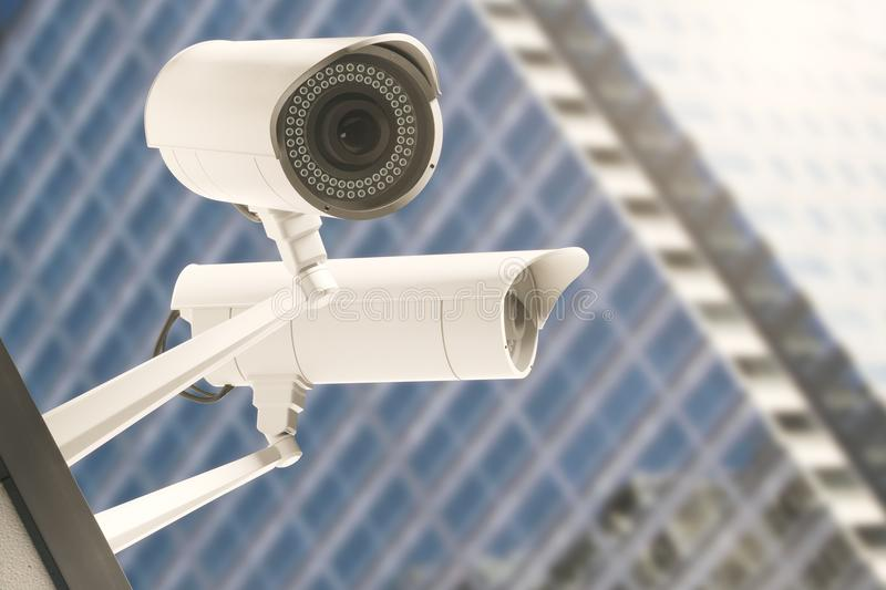 Alertness concept. Close up of CCTV cameras with blurry modern glass building in the background. Alertness concept. 3D Rendering vector illustration