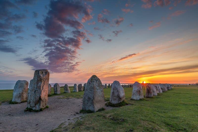 Ales Stenar - en forntida megalitisk stenskeppmonument i sydliga Sverige som fotograferas på solnedgången arkivfoto