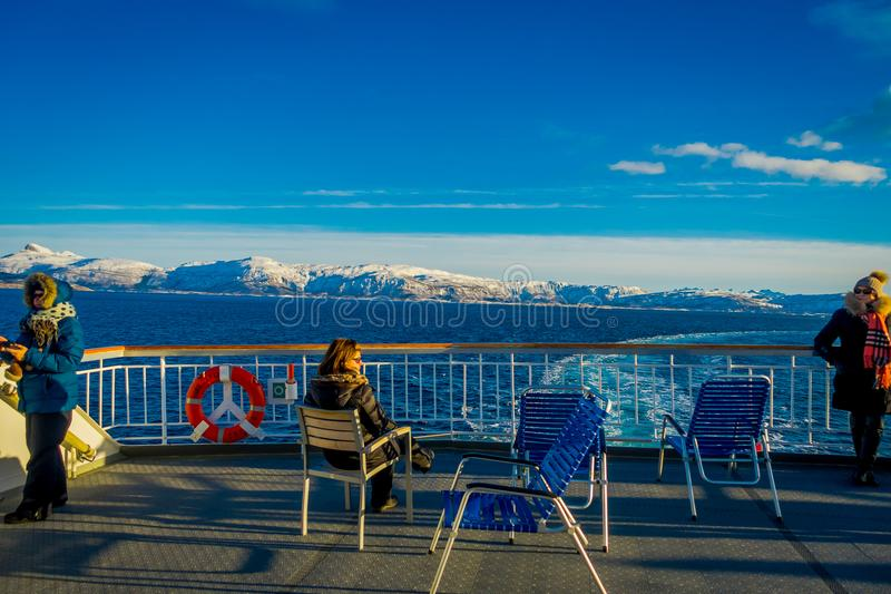 ALESUND, NORWAY - APRIL 09, 2018: Outdoor view of unidentified people sitting and enjoying the landscape in Hurtigruten. Voyage in ferry along Norwegian coast stock images