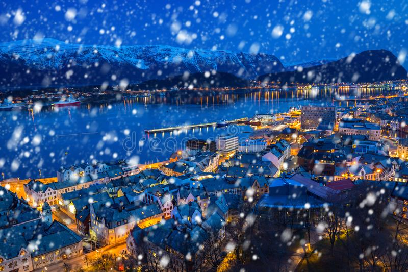 Alesund town on a cold winter night. With falling snow, Norway royalty free stock image