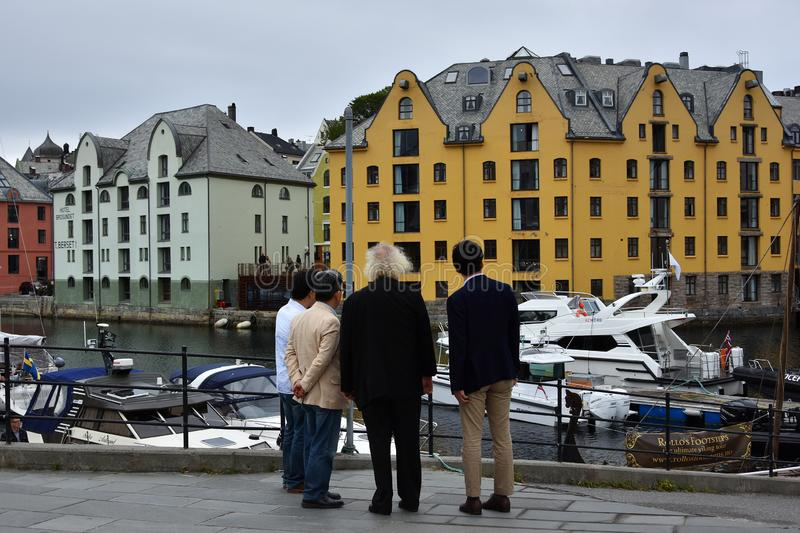 Alesund town and port, More og Romsdal, Norway. ALESUND, NORWAY - JULY 6, 2018. People looking to the view in Alesund town and port, More og Romsdal , on the royalty free stock photos