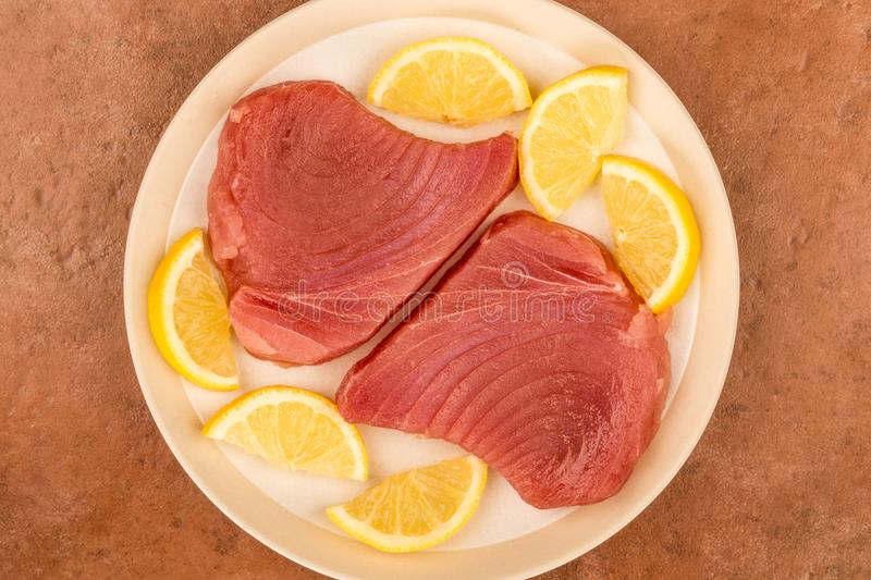 Aleta amarilla cruda cruda fresca Tuna Steaks With Lemon Slices foto de archivo