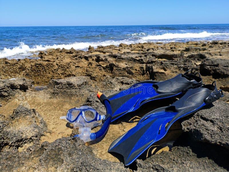 Aletas e máscara azuis para a mentira mergulhando, de mergulho na costa de mar com ondas e o céu azul no fundo imagens de stock