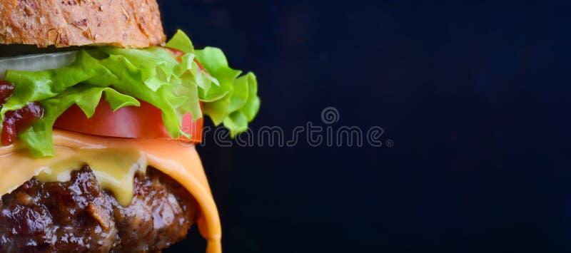 Aletta di filatoio dell'hamburger Hamburger del formaggio con gli anelli arrostiti della carne, del formaggio, del pomodoro, dell immagine stock