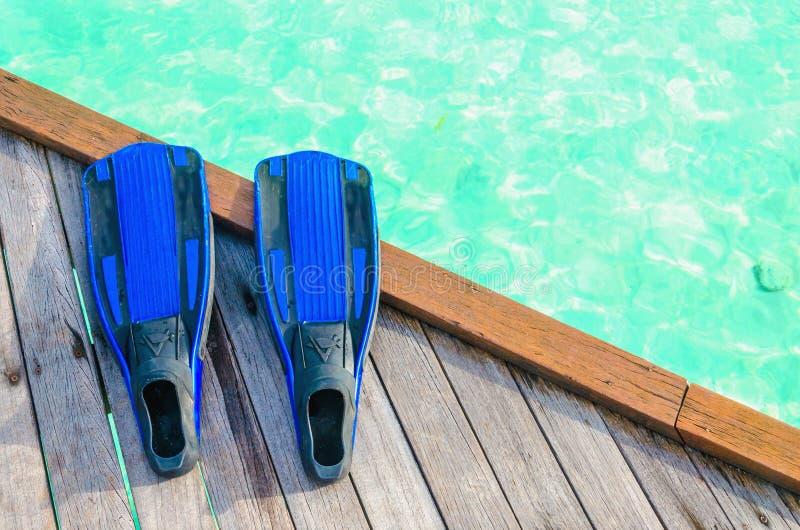 Alette blu per l'immersione su un pilastro di legno contro lo sfondo di acqua azzurrata immagini stock