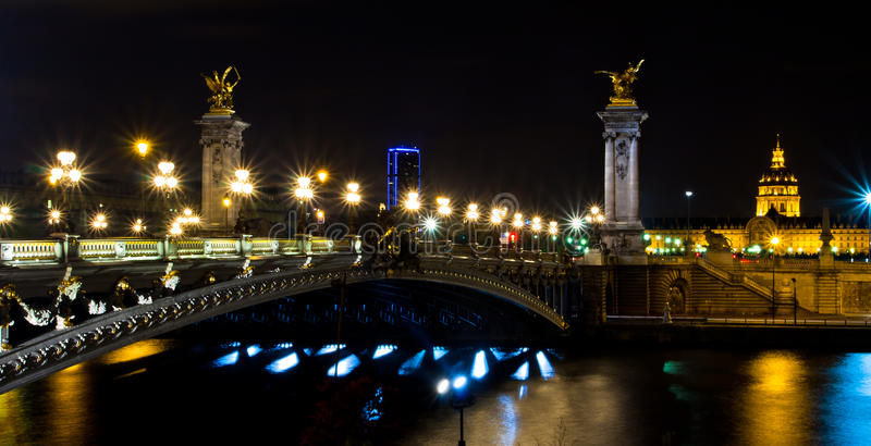 The Alexander III bridge and the dome of the Invalides at night royalty free stock photos